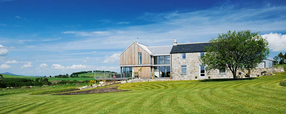 A granite farmhouse with a timber clad extension