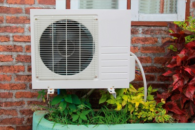 air source heat pump on an external brick wall