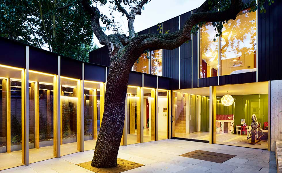 Pear Tree House contemporary home with a courtyard at dusk