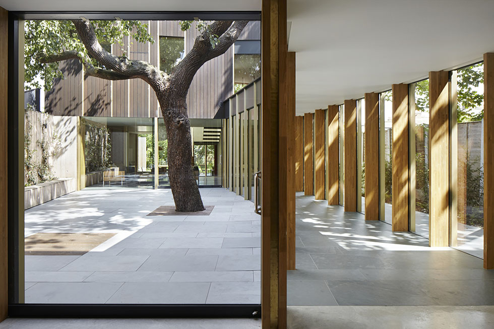 glazed corridor and concrete flooring with tree in courtyard