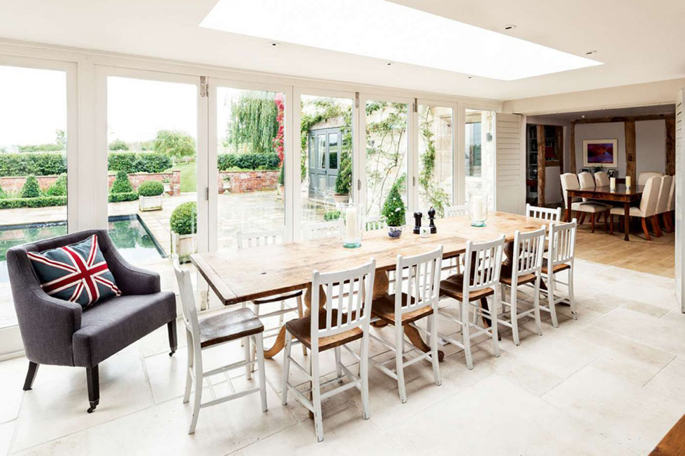 Positioned at the centre of this property, a long dining table in the living kitchen area is the perfect setting for a dinner party, with bi fold doors that open on to the patio. View Project →