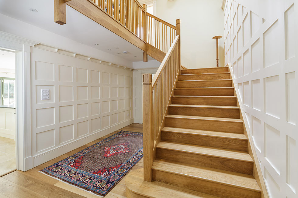 wooden staircase in arts and crafts self build with panelled hallway