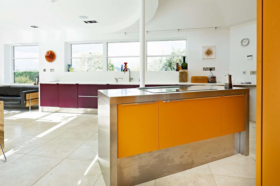 The striking combination of orange and aubergine brings vivid colour to the open plan Effeti kitchen, where a curved ceiling effect adds interest. View Project →