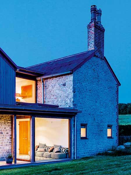 Old cottage extension glazed corridor lit at night