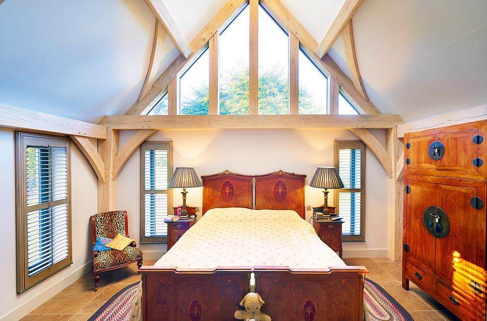 Oakwrights timber frame home bedroom with glazed pitch
