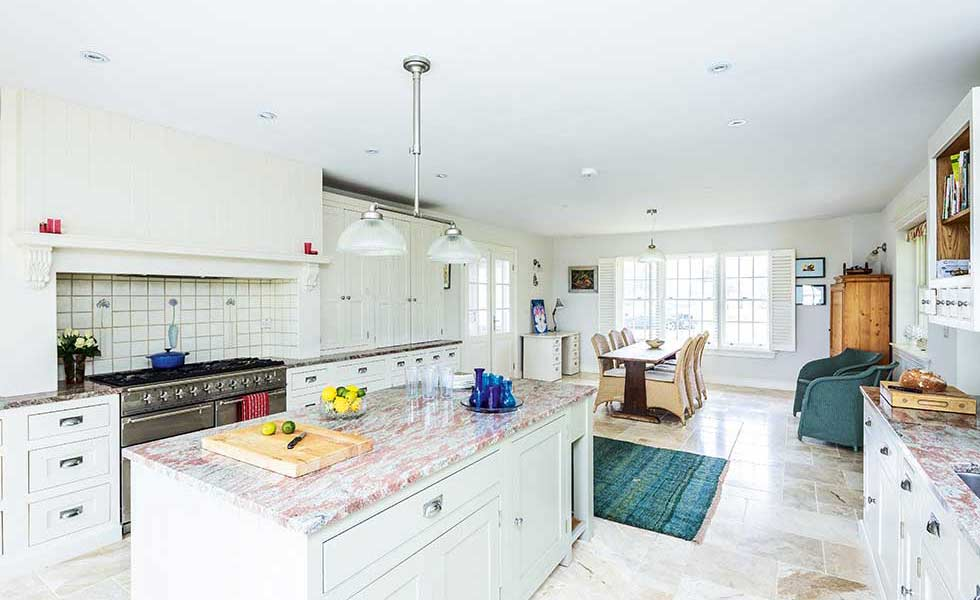 american-style kitchen diner with stone worktops and flooring and white cabinets