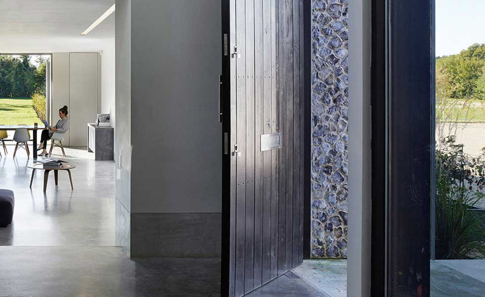 front door of modern home showcasing open plan inside and stone finish