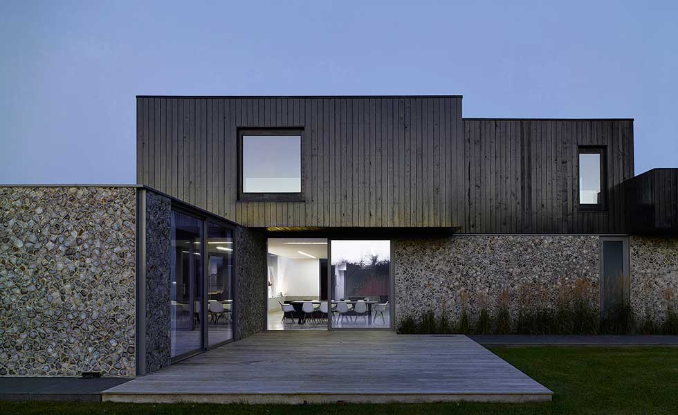 contemporary boxy home with wooden panel and stone finish as well as sliding glass doors
