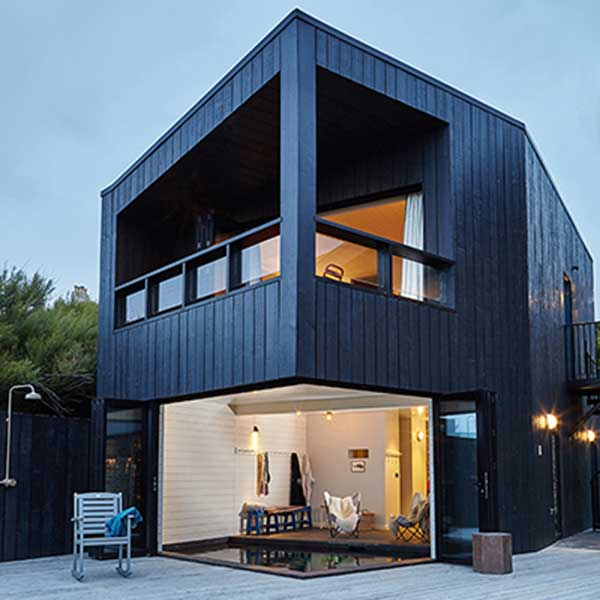 square contemporary home with black panels, balcony and sliding corner door