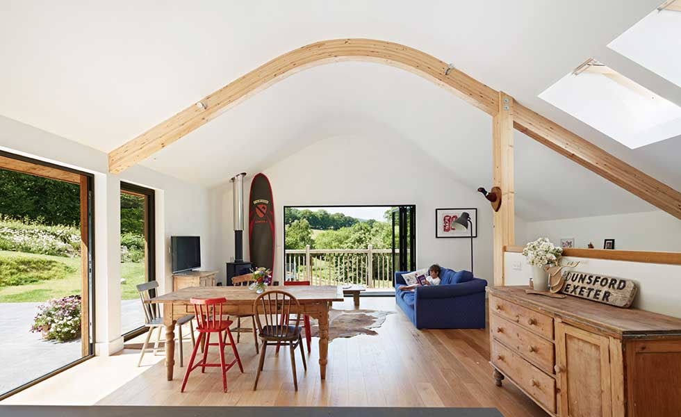 living room with white curved ceiling and wooden beams and collection of mismatching wooden furniture