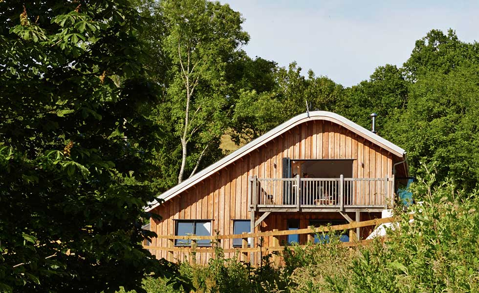 curved roof wooden panelled home with balcony and surrounded by green space