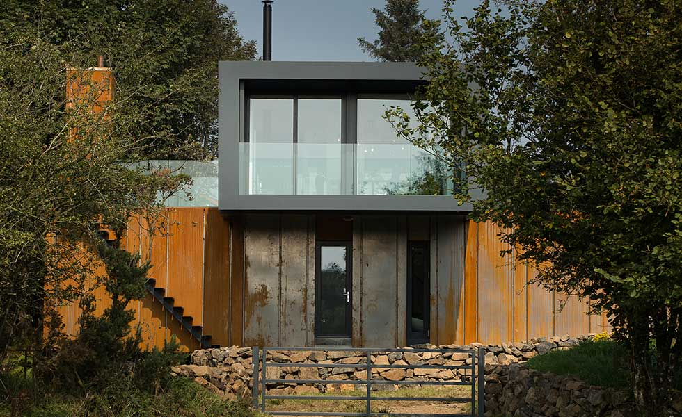 front shot of shipping container house with glass balcony