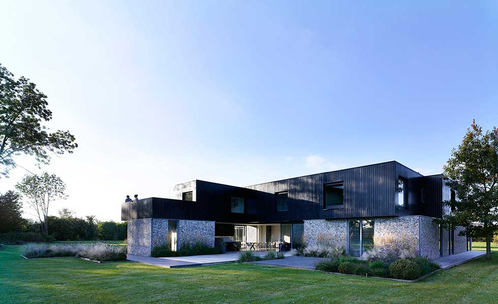 view of contemporary boxy shaped home with wooden paneling and stone finish also featuring a balcony