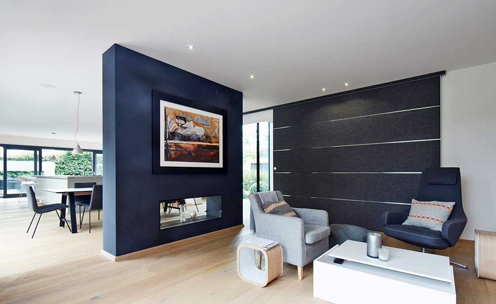 modern black open plan living space with grey armchairs