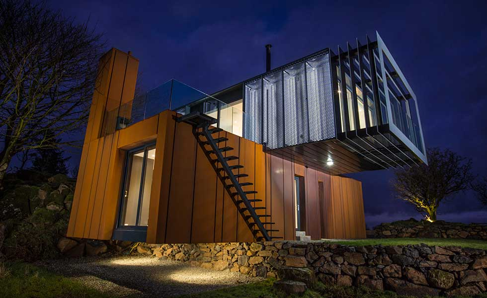 night shot of shipping container home with over extending balcony