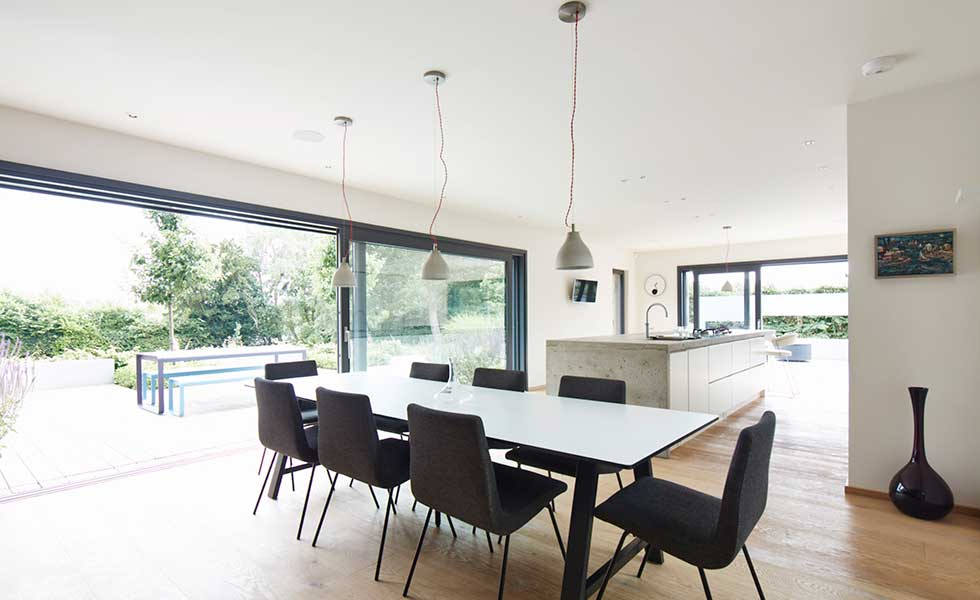 open plan dining space with large dining table and glass sliding doors