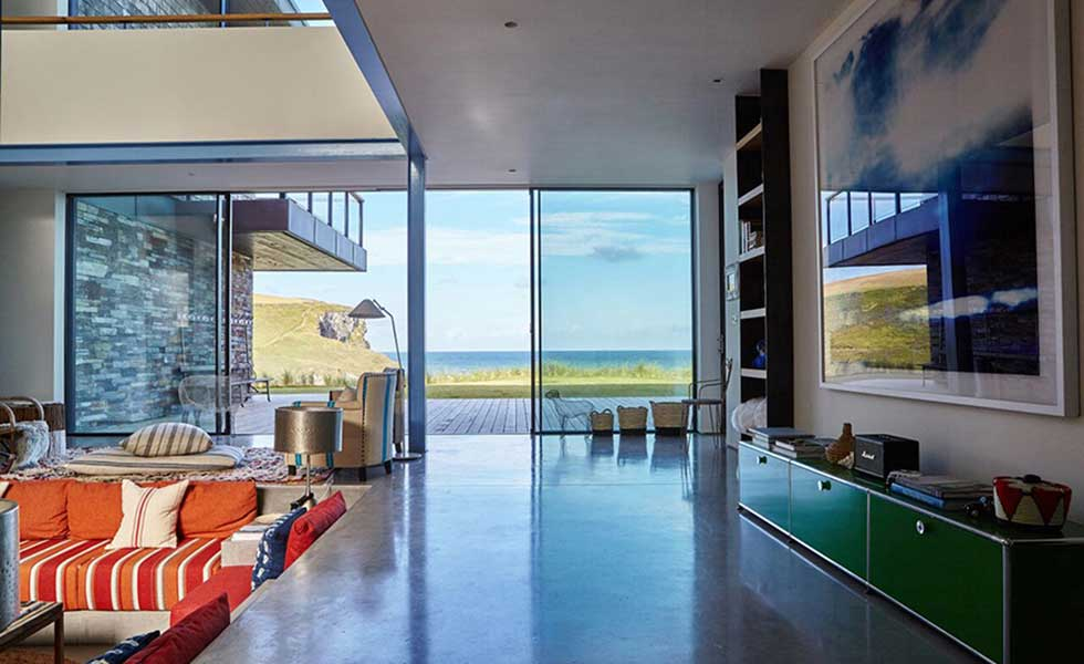 open plan living space with glass sliding doors overlooking sea view