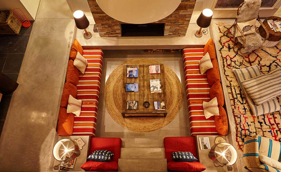above shot of built in living space with red striped settees and large wooden coffee table