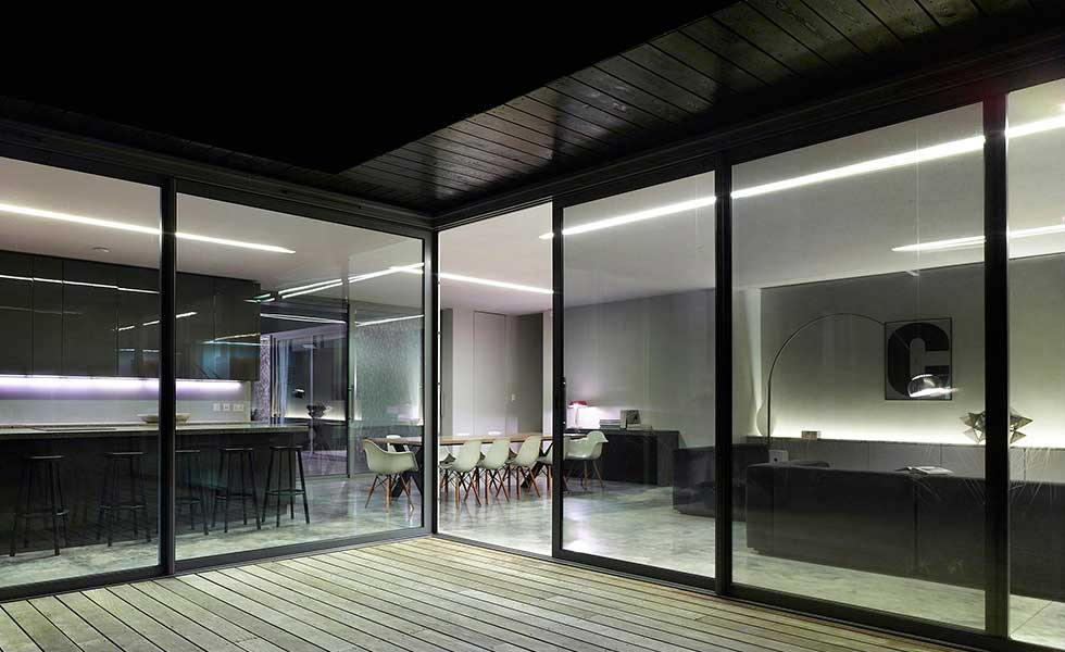 sliding glass doors looking into dark interior of a contemporary open plan living space