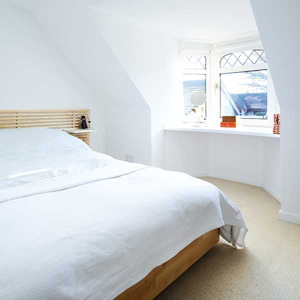 white bedroom with white bedding and wooden bed frame