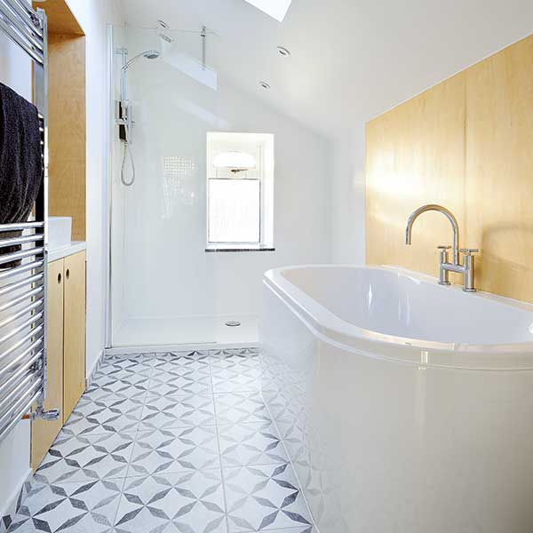 white bathroom with wooden panelling, white and grey patterned tiles and freestanding bath