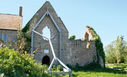An old building that has been propped up with a wooden arm to prevent further subsidence