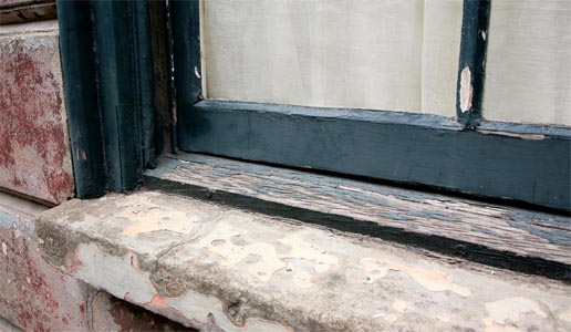A worn wooden window frame and stone sill