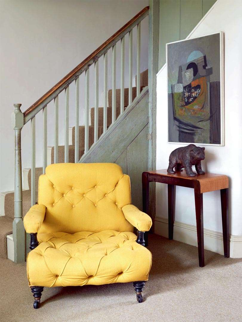 Yellow chairs by stairs in renovated schoolhouse