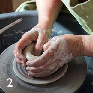 Throwing and centering the clay on the wheel