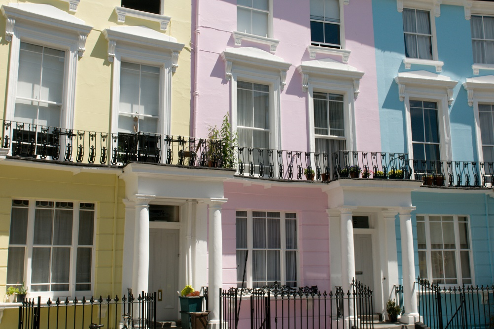 a colourful street in Camden, London with a yellow house, pink house and blue house