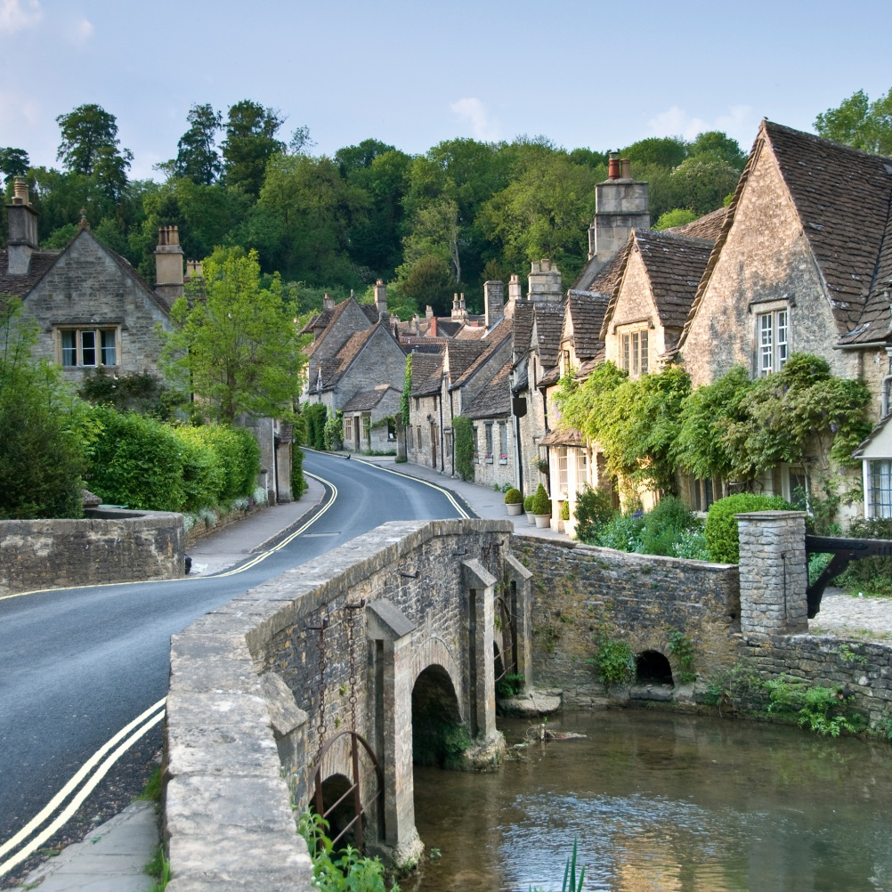 a tranquil conservation area village with stone cottages and a river over a bridge