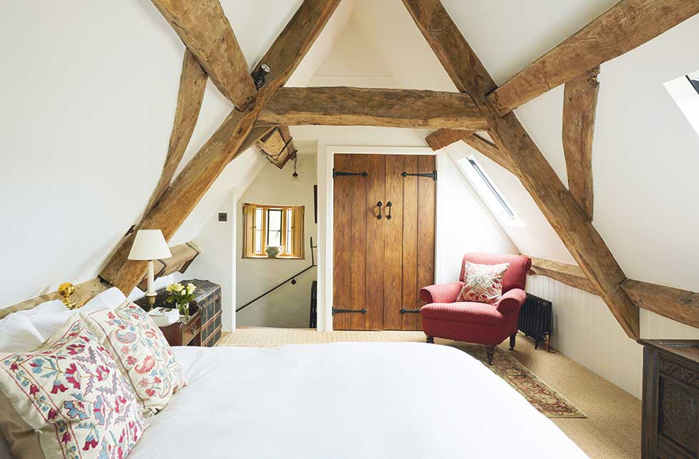 a bedroom in loft space with exposed beams