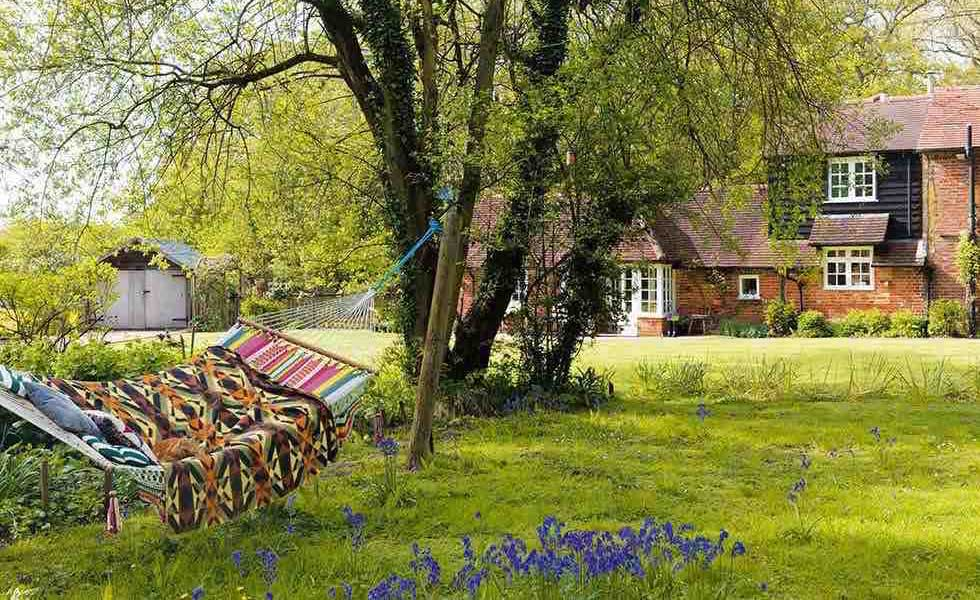 a hammock in an English country garden full of bluebells