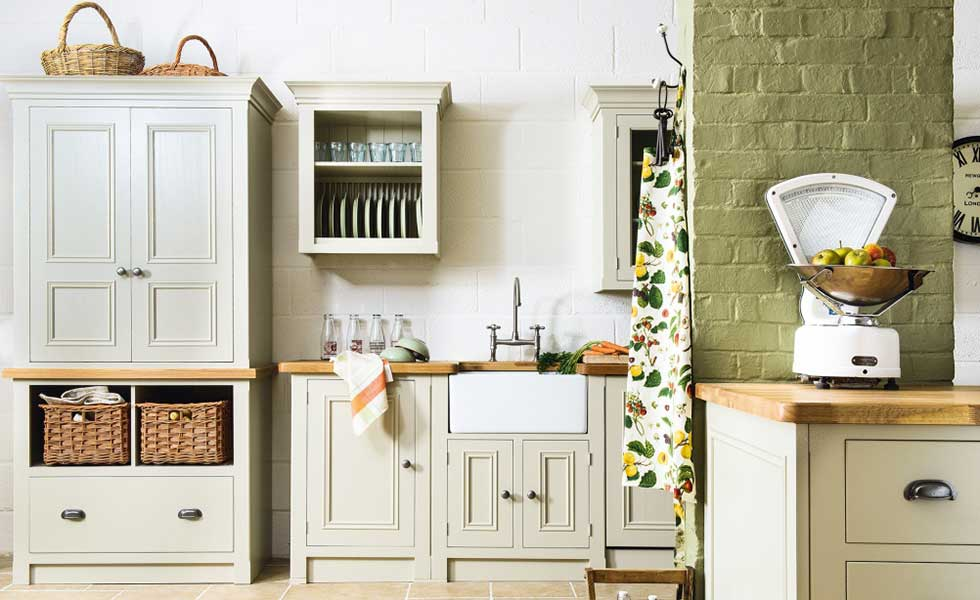 kitchen in shades of green with deep sink and apples on scales