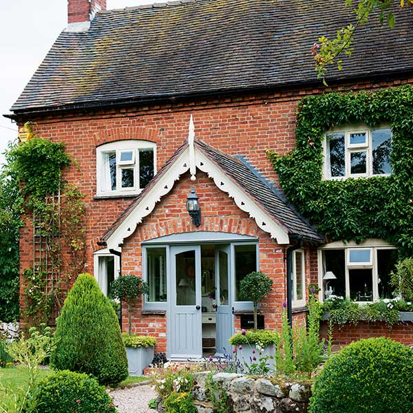 red brick farmhouse with large central porch, white coving and light blue front door
