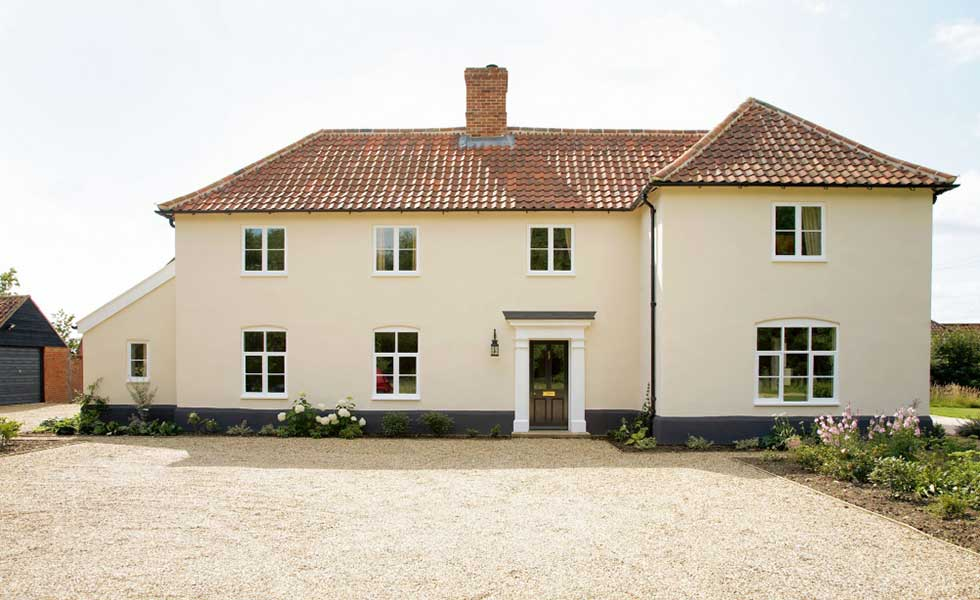 large restored Georgian farmhouse with white walls and red roof