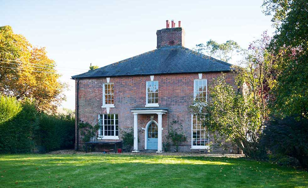 large stand alone farmhouse with central placed chimney and porch way, with blue front door and large windows
