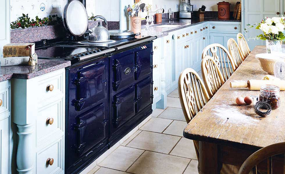 traditional wooden table covered in flour for baking, with range cooker and light blue cabinets