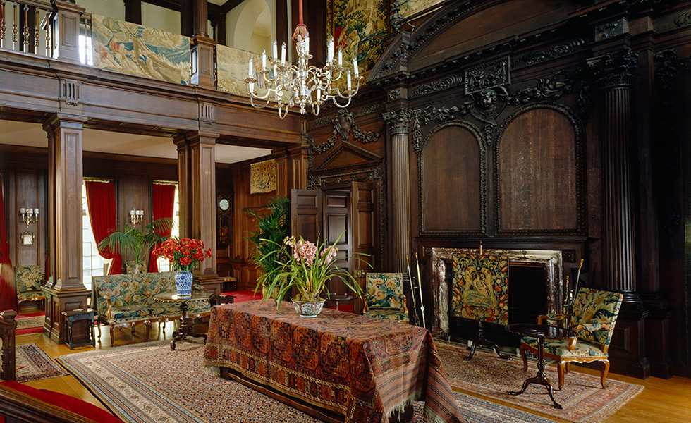 The Hall at Polesden Lacey, showing the chandelier and the woodwork on the fireplace wall