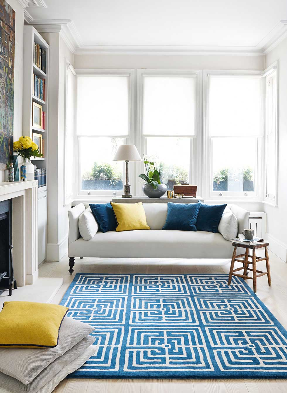 Open plan living room with blue rug by Jennifer Manners