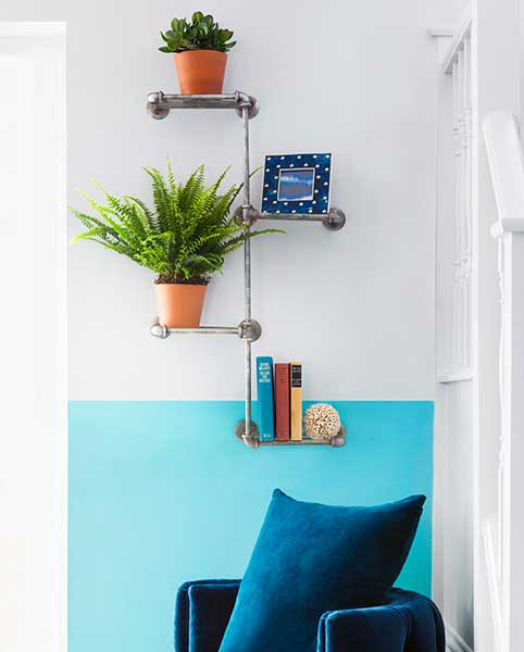 shelving made from pipes in turquoise living room with plants