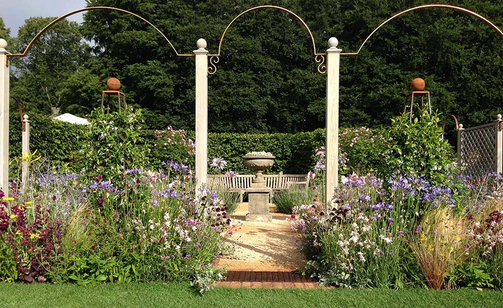 traditional english country garden with pedestal and arches