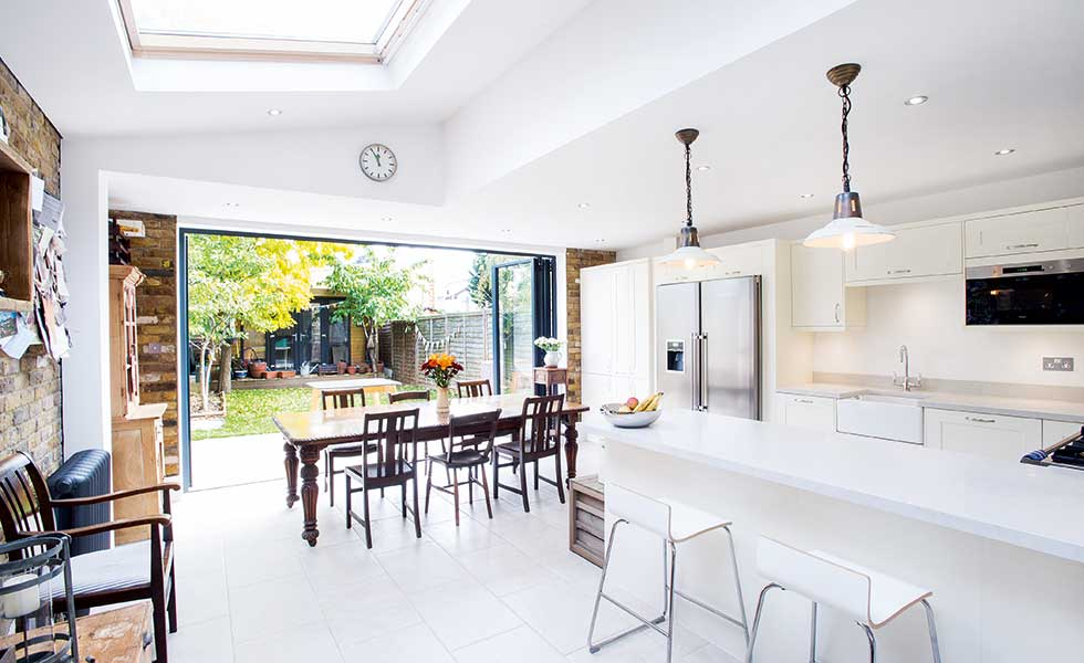 kitchen diner extension with white units and bi fold doors onto the garden