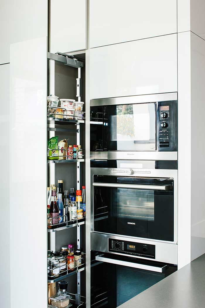 built in floor to ceiling larder and built in miele appliances in an architectural kitchen extension