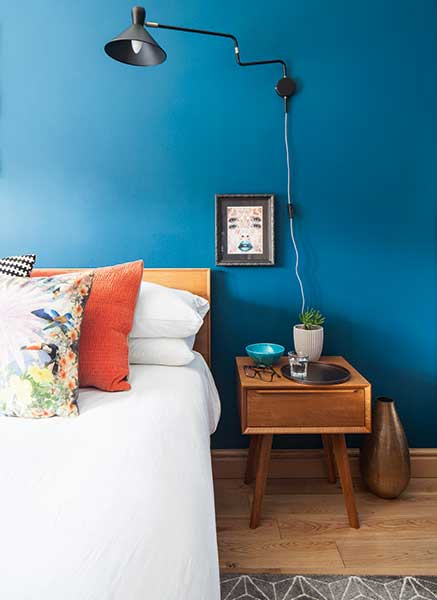 retro style bedside table and bed in blue bedroom