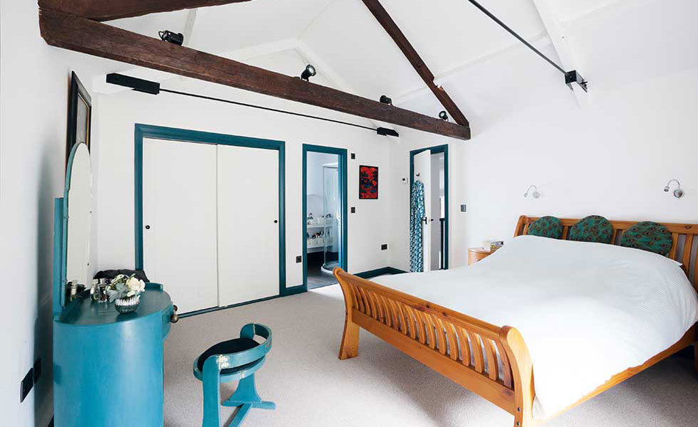 simplistic blue bedroom in a converted coach house