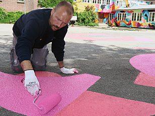 Gatekunstner David Stenmarck fortsetter veggmaleriet på Tyskerbrakka (i bakgrunnen) ut i en horisontal klatrevegg og andre spill på asfalten.