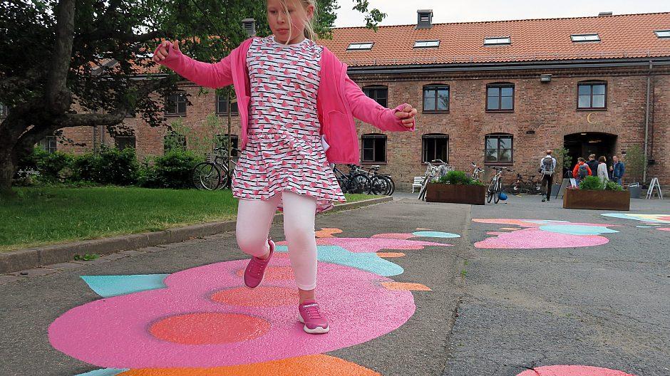 Asfalten er blitt morsom og forandret til en fargerik klatrevegg som Mari 8 år forserer i fullt firsprang.
