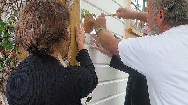 Kristin Tveit, Svein Sæterdahl og Ellen S. de Vibe skrur opp plaketten med 100 000 adresser på hytteveggen.