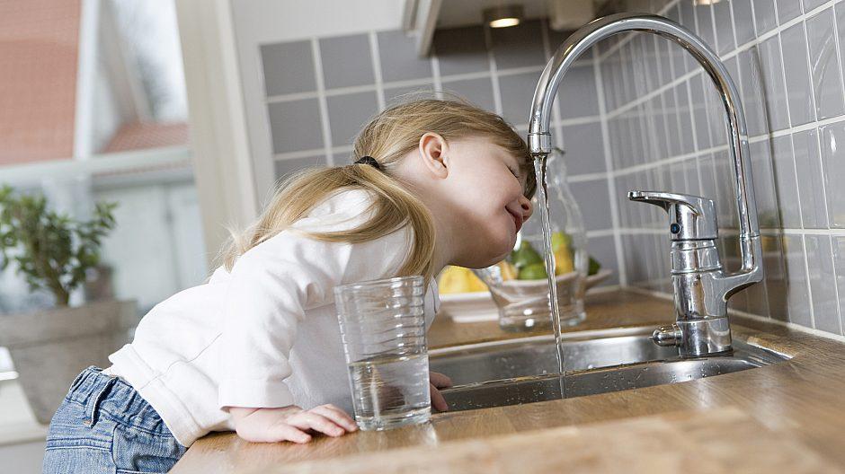 Jente som drikke vann fra springen